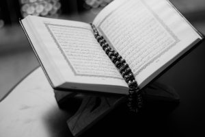 A black and white photo of a Quran with prayer beads placed in the center