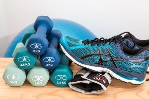 Exercise equipment laid on a table. There are 2 kg weights and exercise shoes.