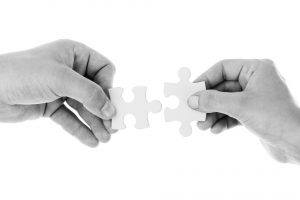 An adult and child putting two pieces of a puzzle together.