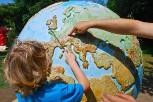 A teacher and a student pointing towards a large globe of the Earth during a lesson.