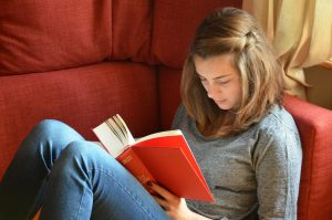 A student reading a book while sitting on the couch.