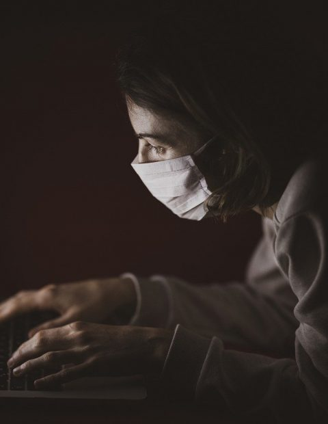 lady wearing face mask at laptop