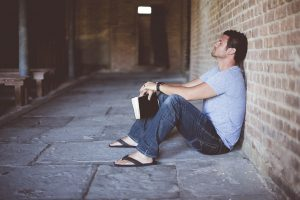 A man leaning against a wall while holding a book (possibly a Quran) contemplating about himself